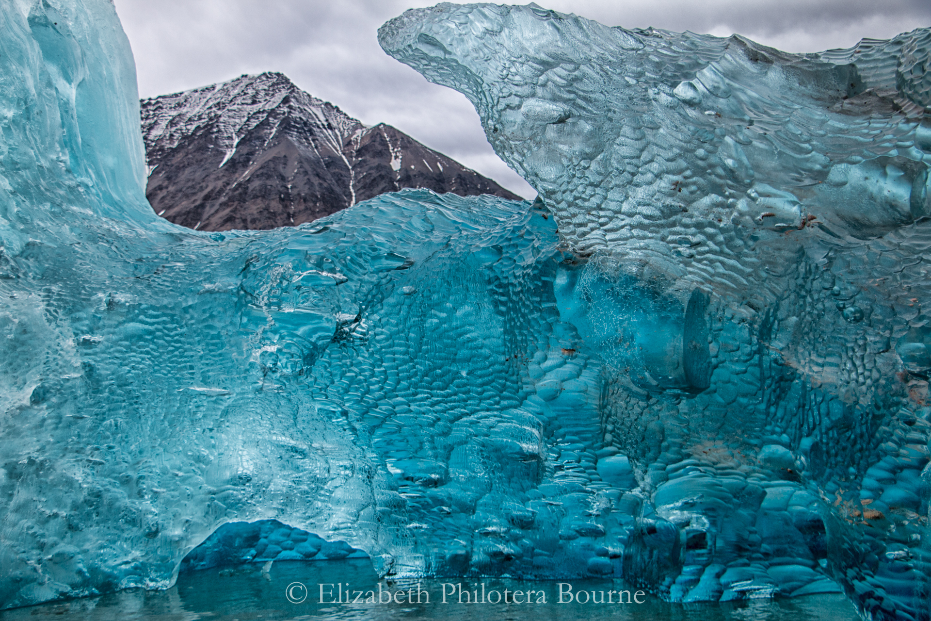 Crystal blue ice revealing mountain top in Spitzbergen