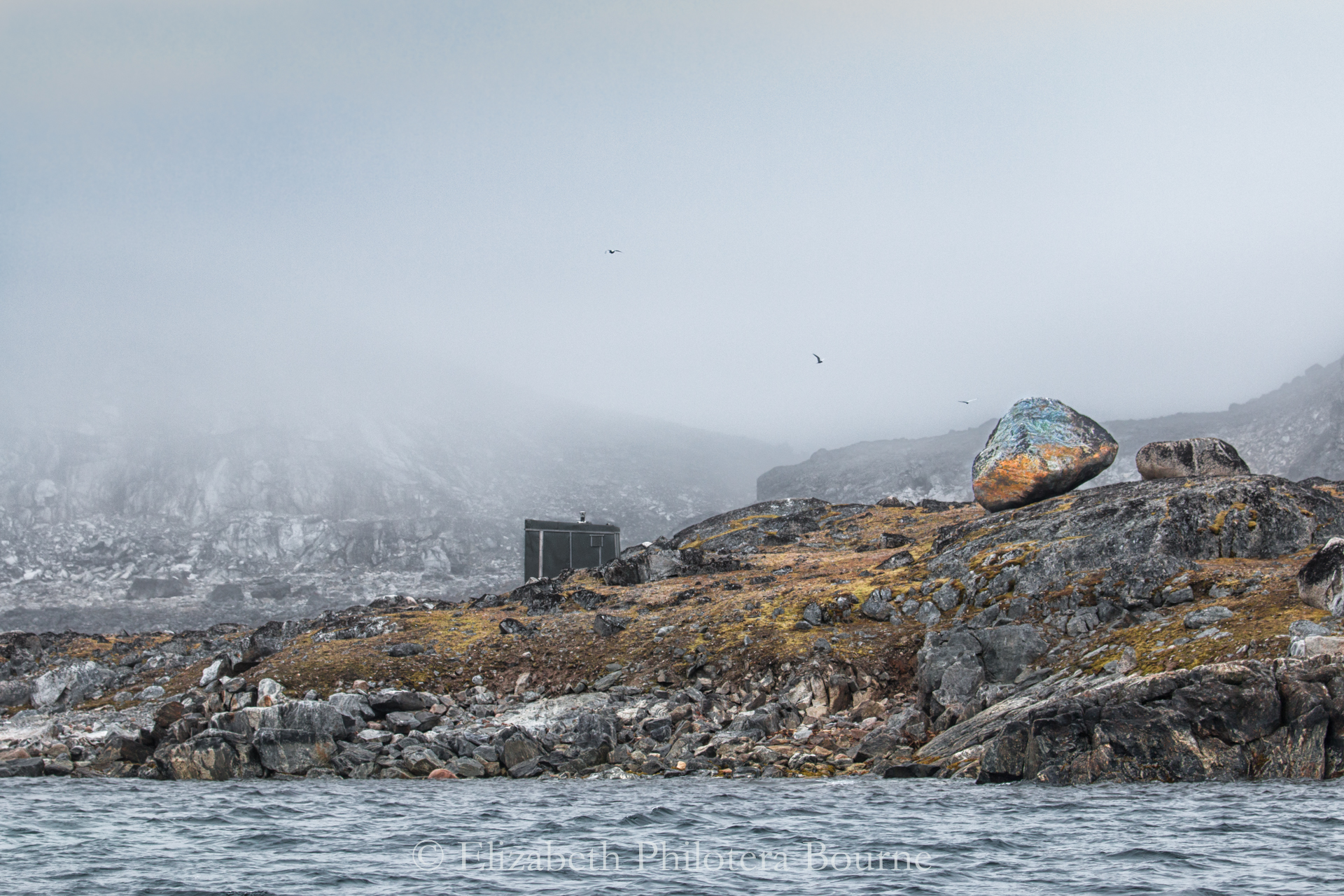 Small hut for a hunter on a peninsula surrounded by glacial errata in Svalbard