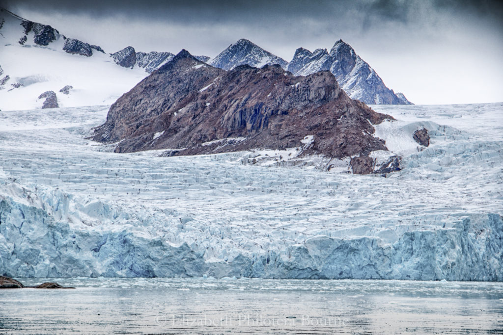 Mountain peaks rising up from glacier ice in Spitzbergen