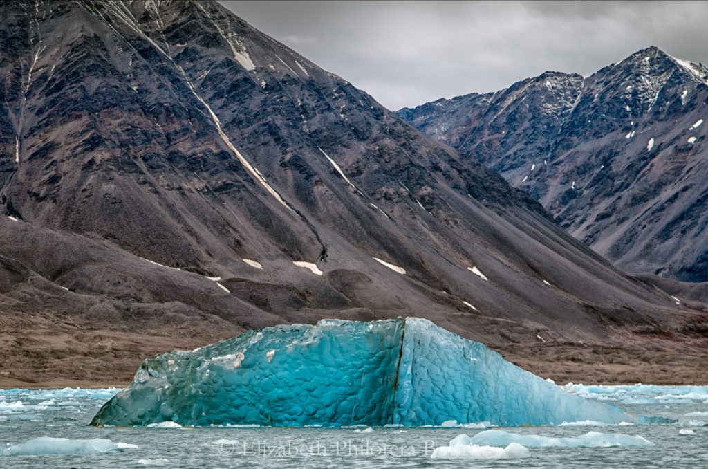 Flipped iceberg showing two tones of blue crystal ice in svalbard