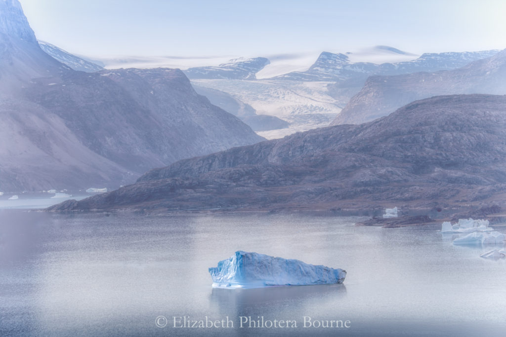 Lone iceberg floating in calm fjord with snow capped mountains and rocky cliffs in Greenland