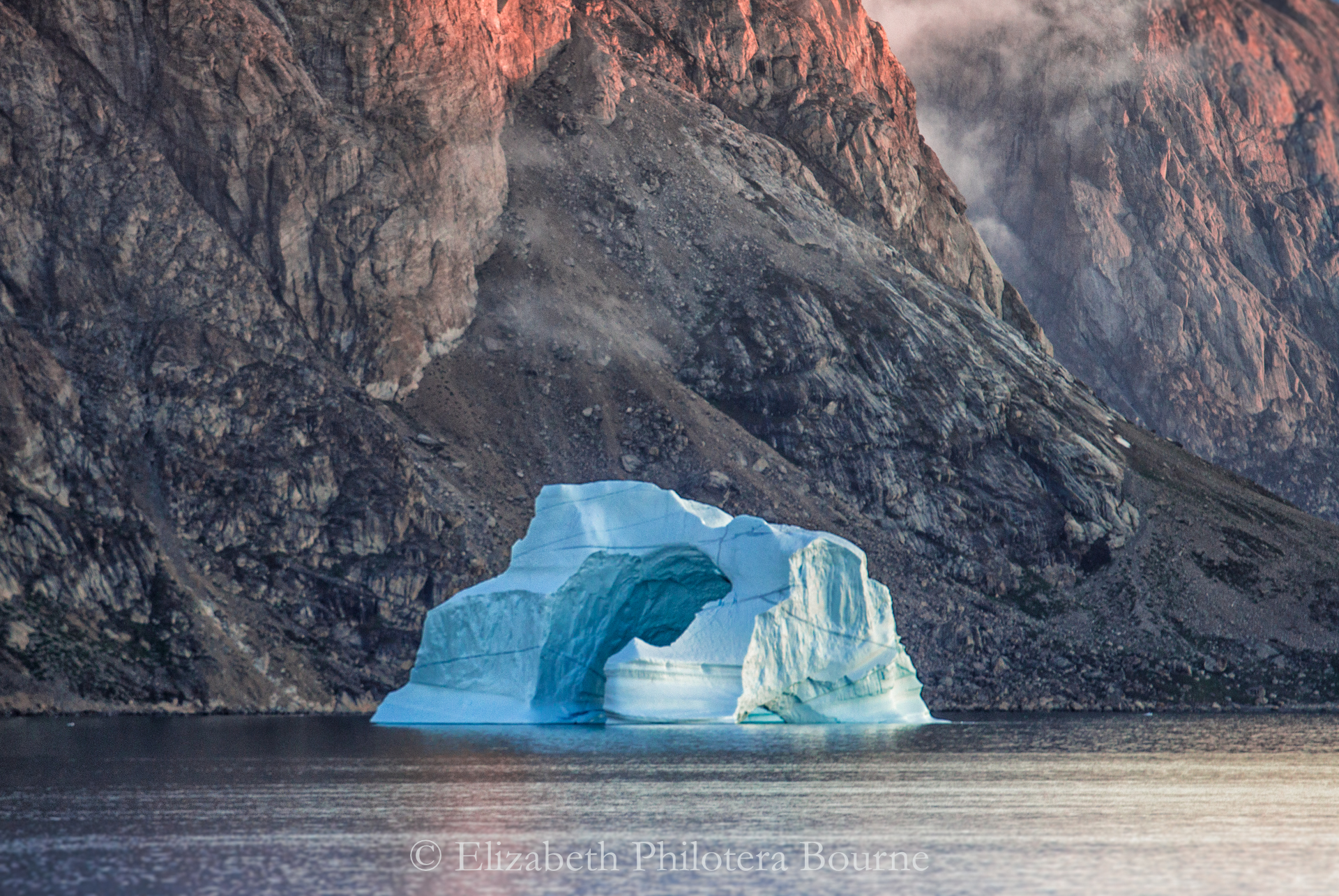 Floating blue iceberg against rocky mountainside with low clouds