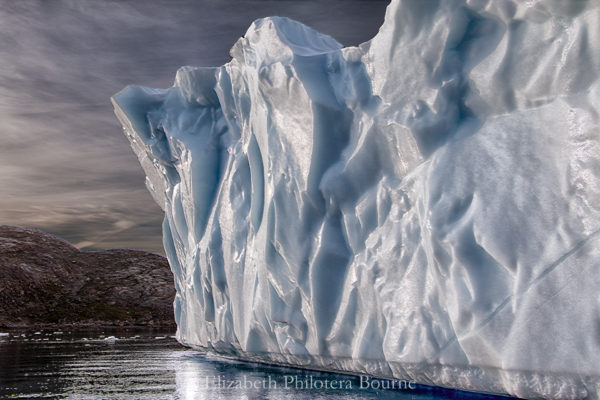 Floating wall of white iceberg against stormy sky and rocky cliffs in Greenland