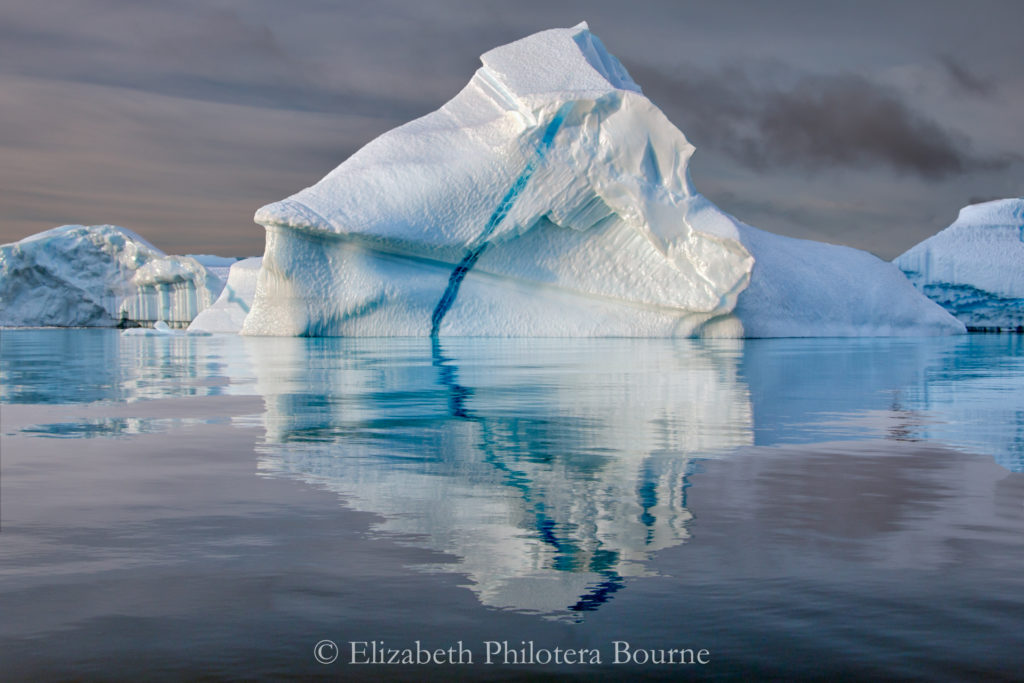 Pinnacle iceberg with blue vein floating in still water with reflection