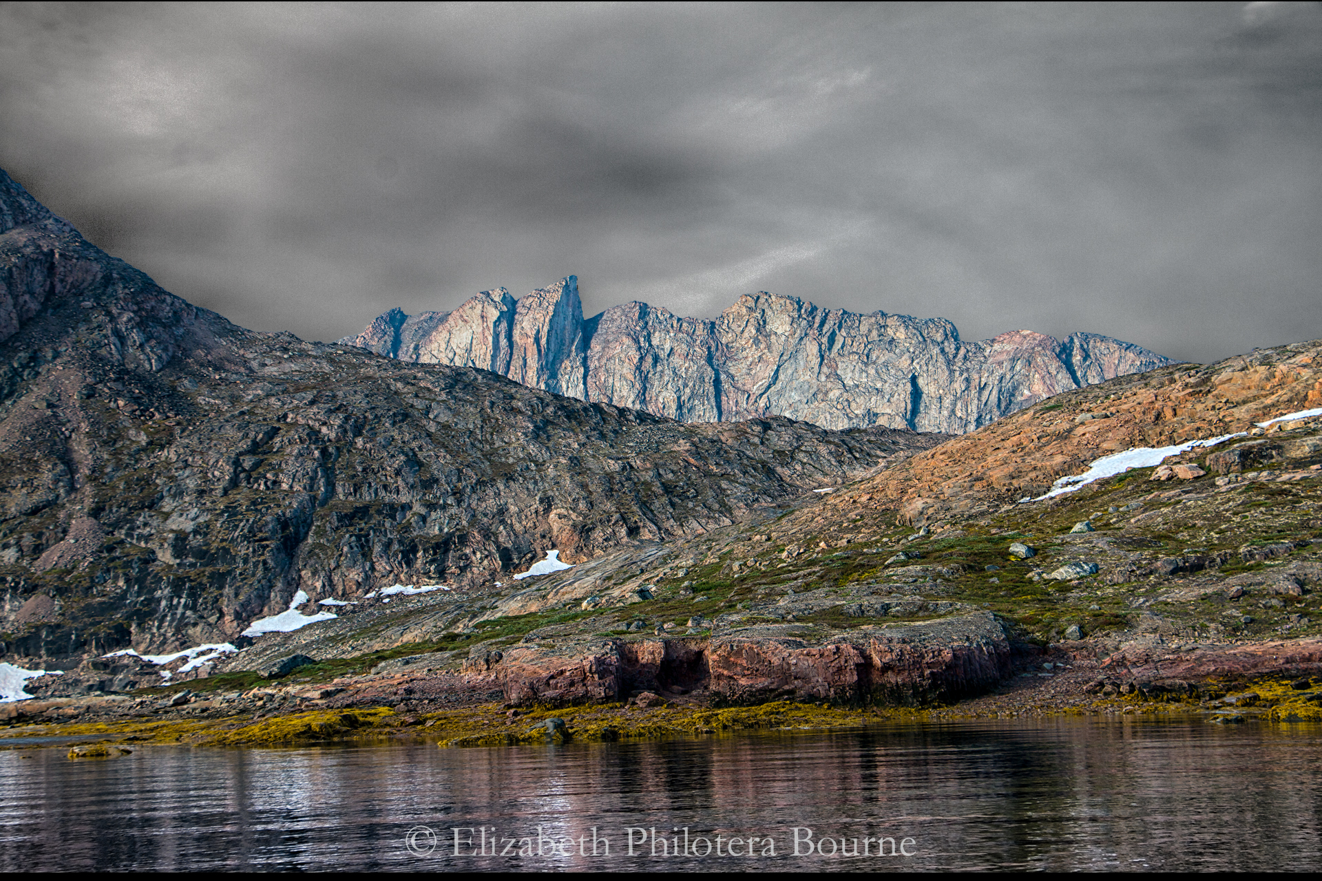 Rocky landscape with gray cliffs against stormy sky in Greenland