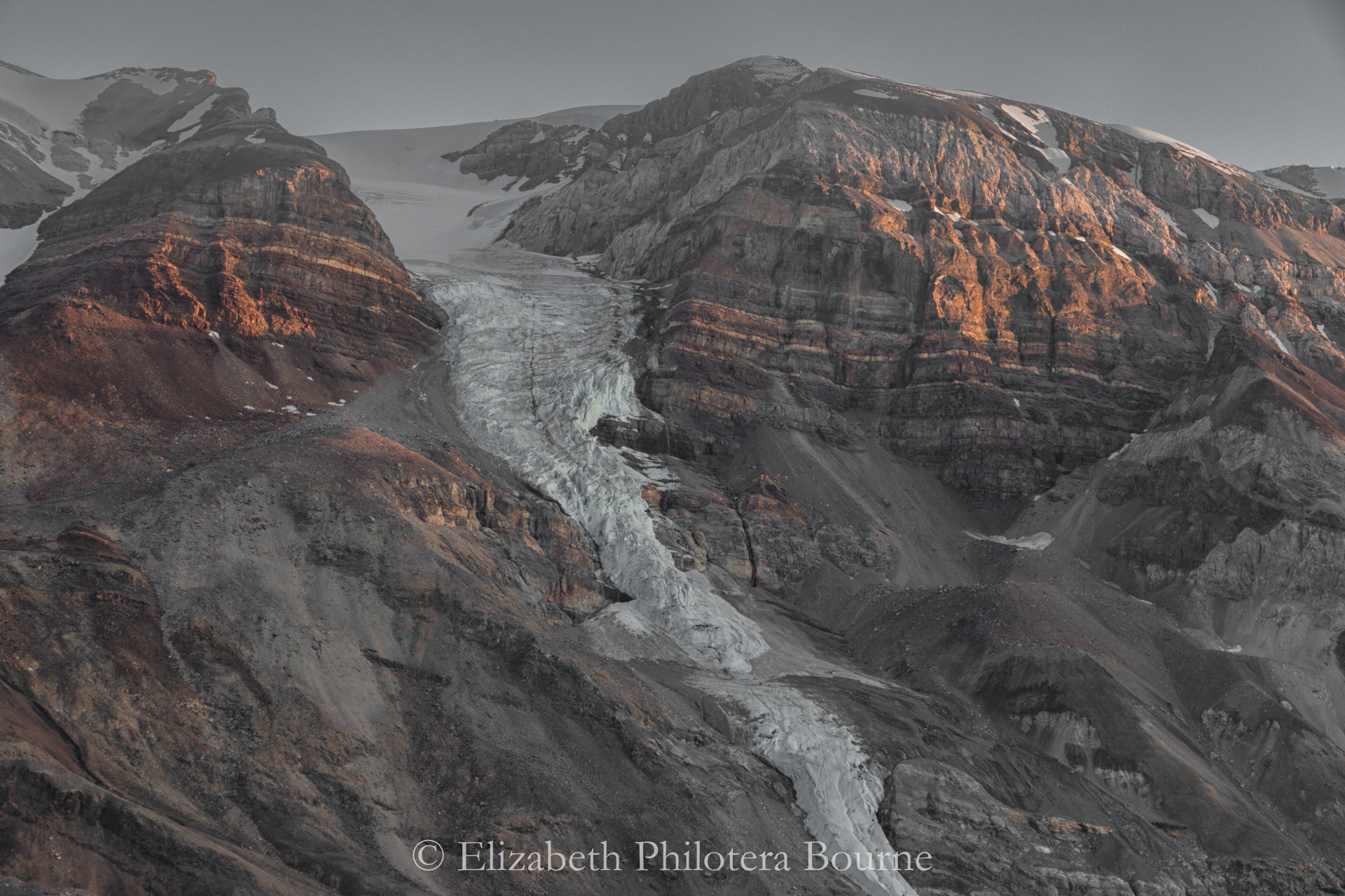 Rocky orange mountainside with remains of melting glacier in Greebland