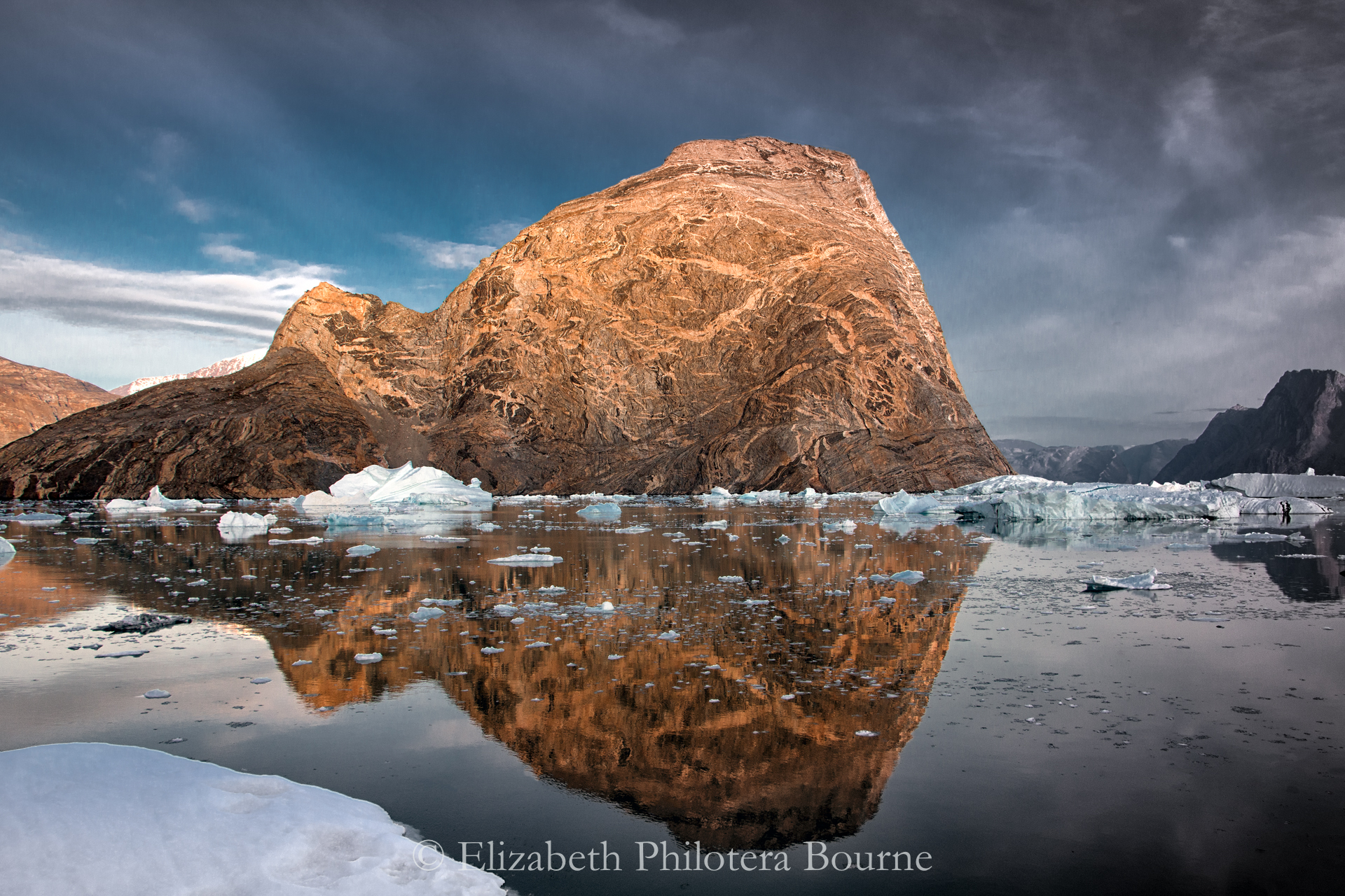 Orange striated rock with dramatic sky reflected in still water with icebergs in Greenland