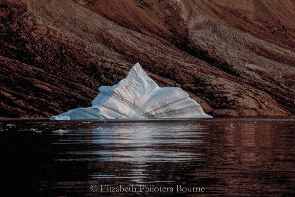 White iceberg floating in black water against orange rocks in Greenland