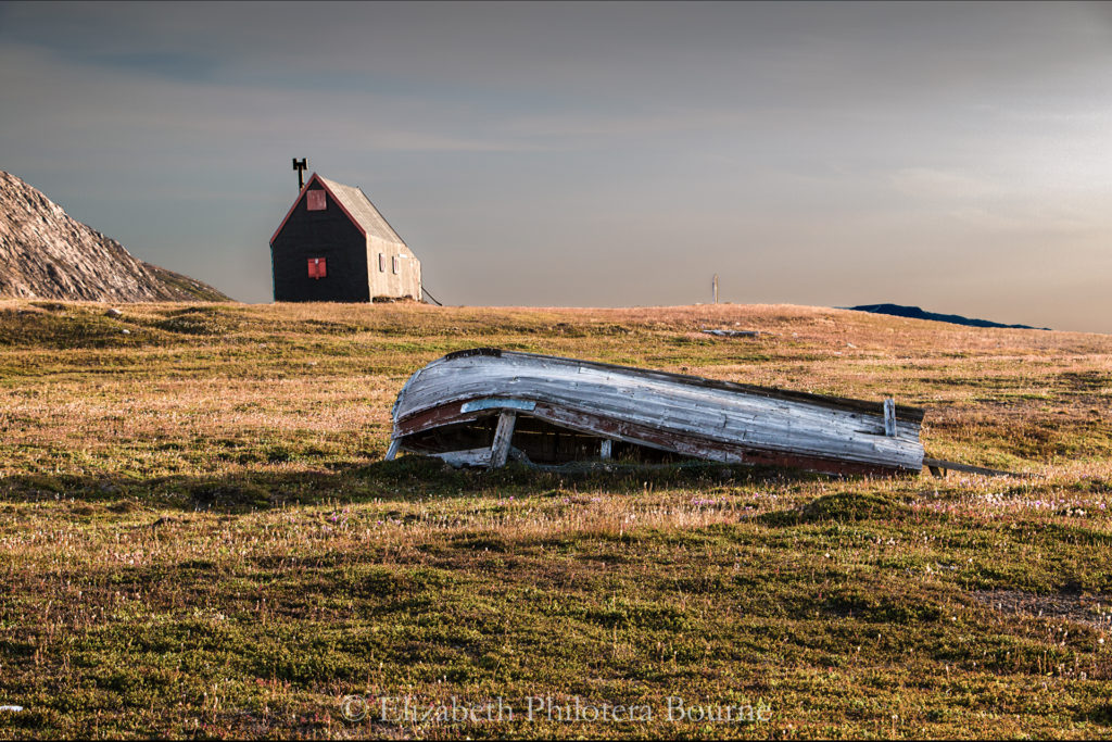 Danish Sirius Patrol black cabin and abandoned boat in Greenland