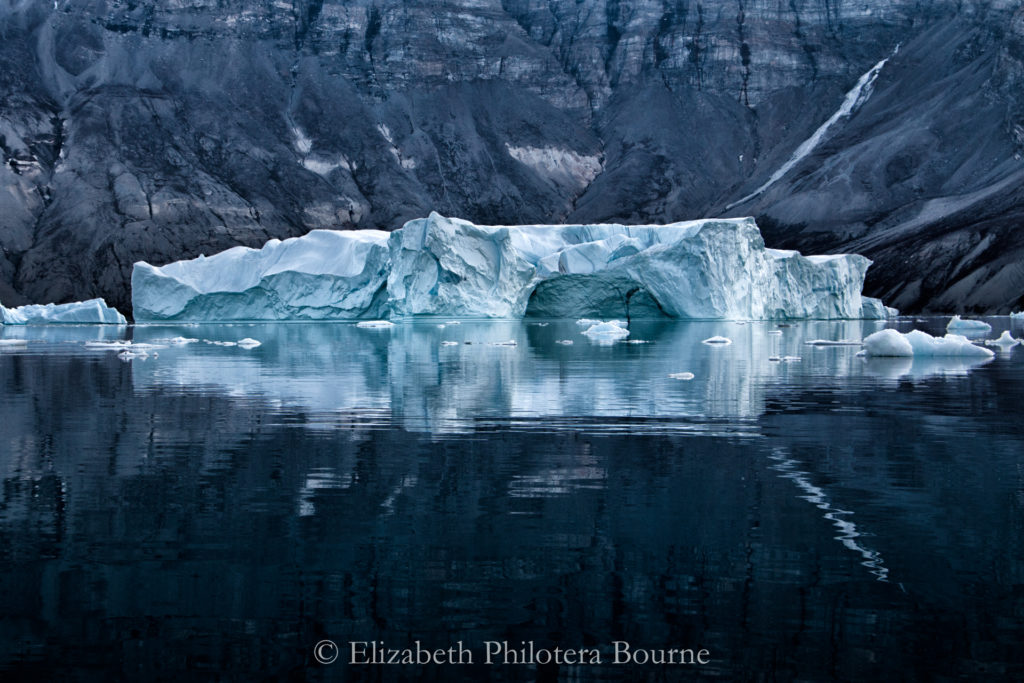 Long iceberg with ice cave and reflection floating on black water with dark gray cliffs behindwater