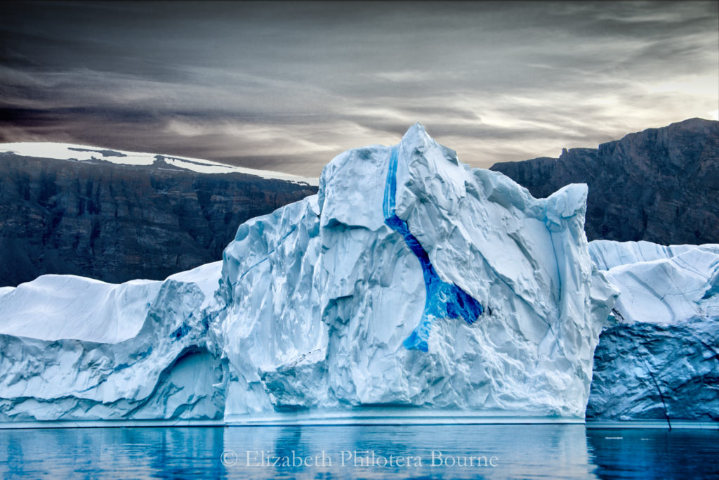 Blue iceber wit intense blue veining floating against dark rocky cliffs and gray sky