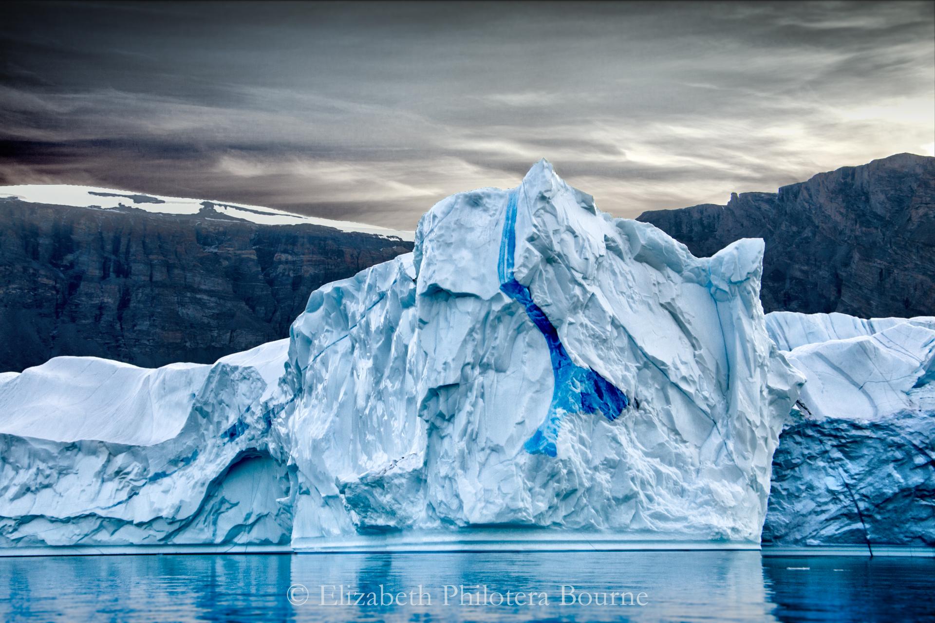 Blue iceber wit intense blue veining floating against dark rocky cliffs and gray sky