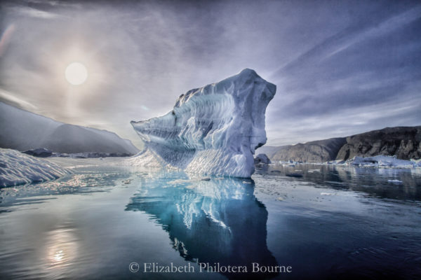 Iceberg with blue reflection glowing in sunlight