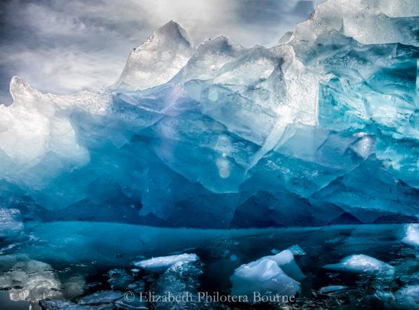 Crystal blue iceberg with sun shining through illuminating floating blue bergy bits