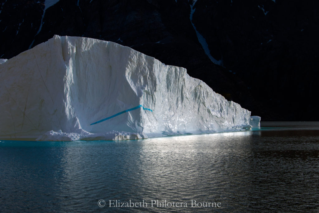 White iceberg floating against black cliff with white reflection glowing in the water in Greenland