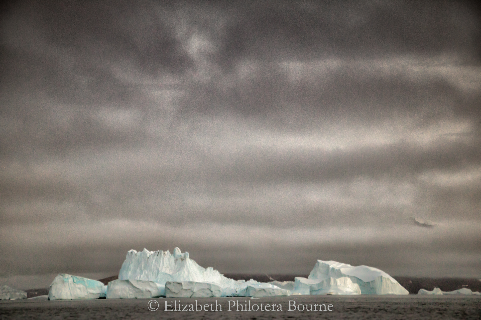 Long white iceberg against a stormy gray sky and ocean in Greenland