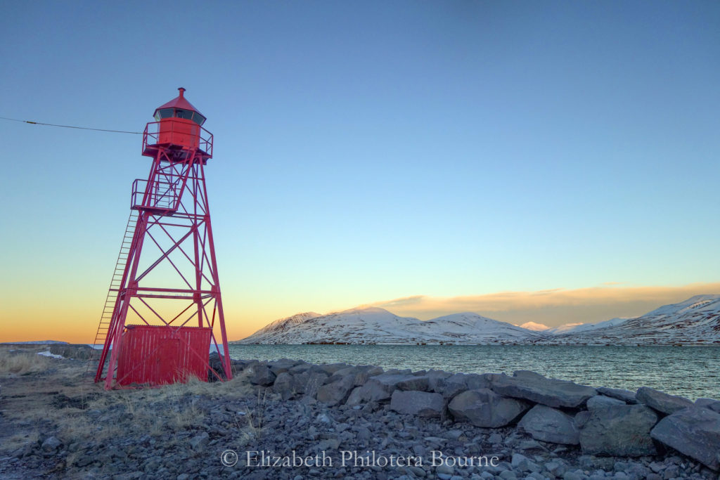 Red beacon along Eyjafjord against clear blue sky in winter in Iceland