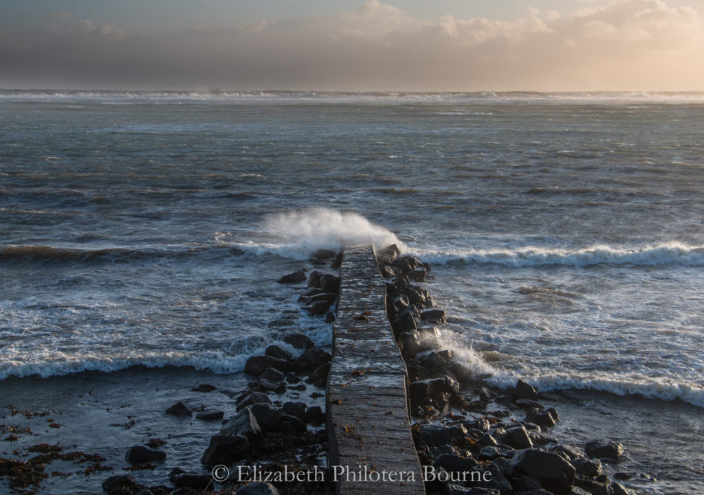 Crashing wave at the end of long pier into winter ocean on the breach at Eyrarbakki, Iceland
