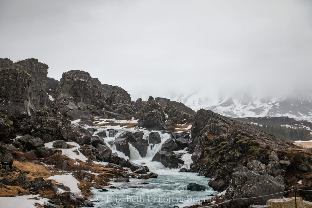 Oxara river in winter surrounded by rocks and fog in Thingvellir
