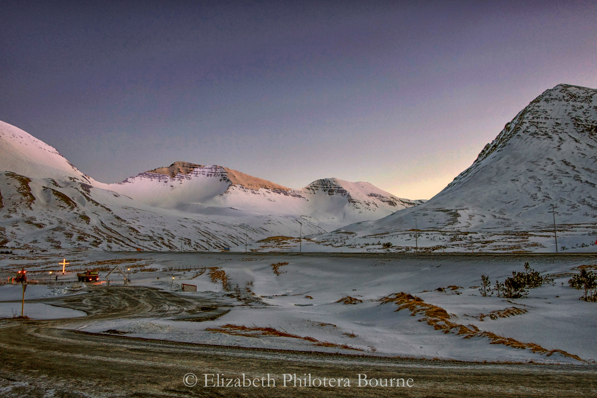 Sunset illuminating snowy mountains and electric cemetary in winter in Iceland