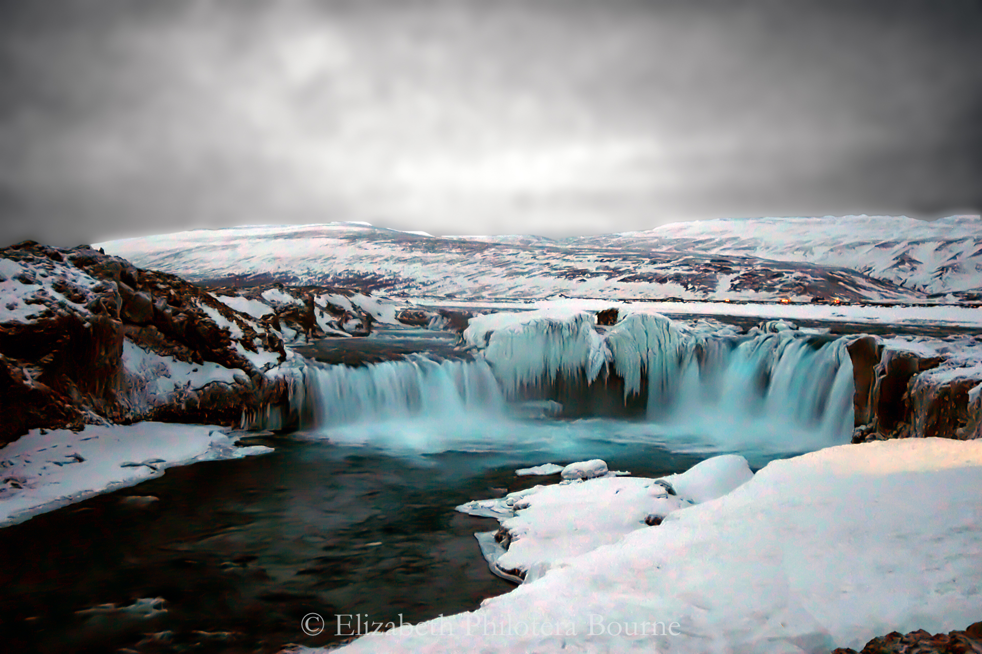 Beautiful, frozen Godafoss waterfall in winter with gray sky and snow