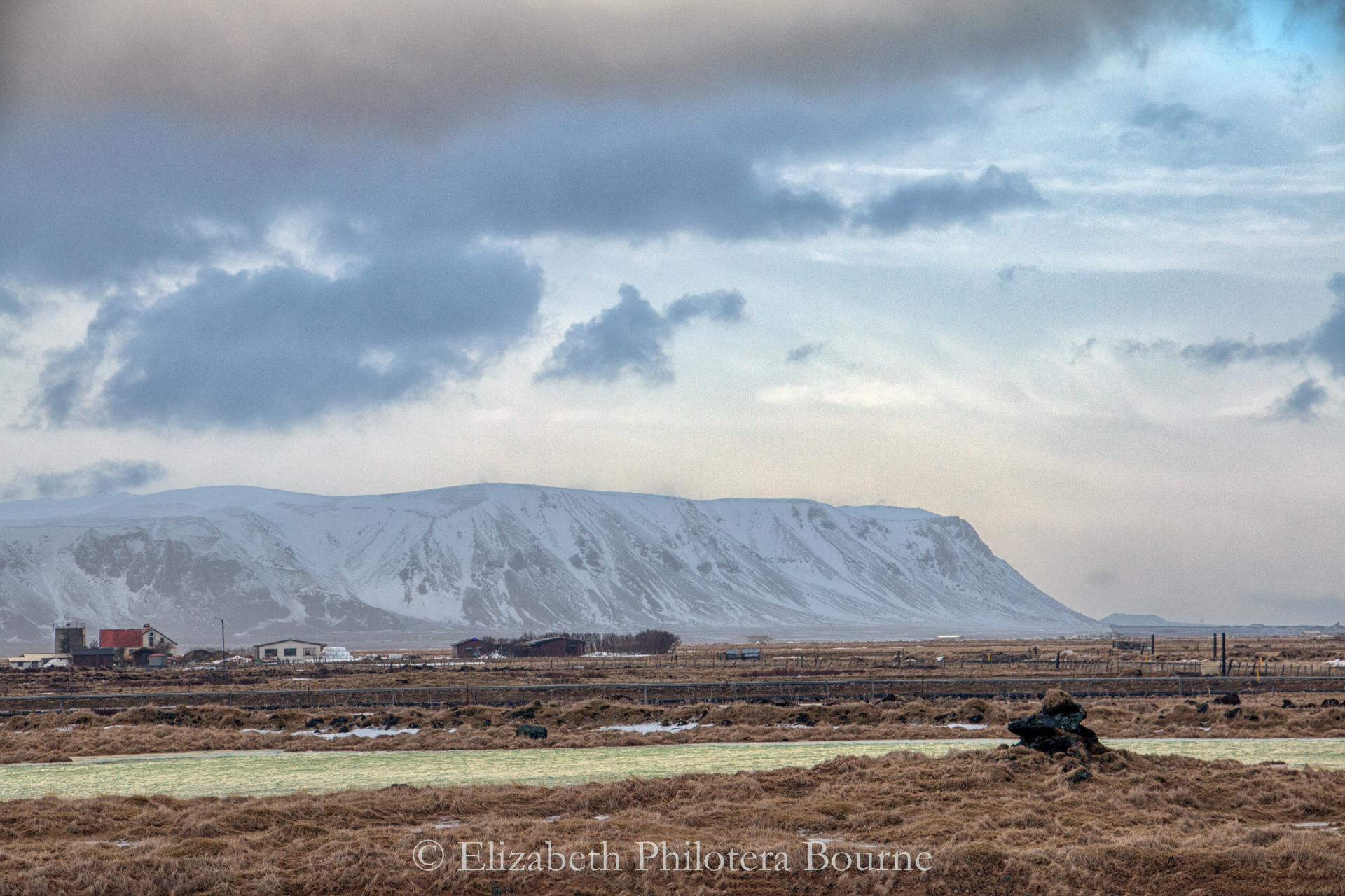 Snow covered Ingolfsfjall mountain across barrent plain with dramatic sky in Iceland