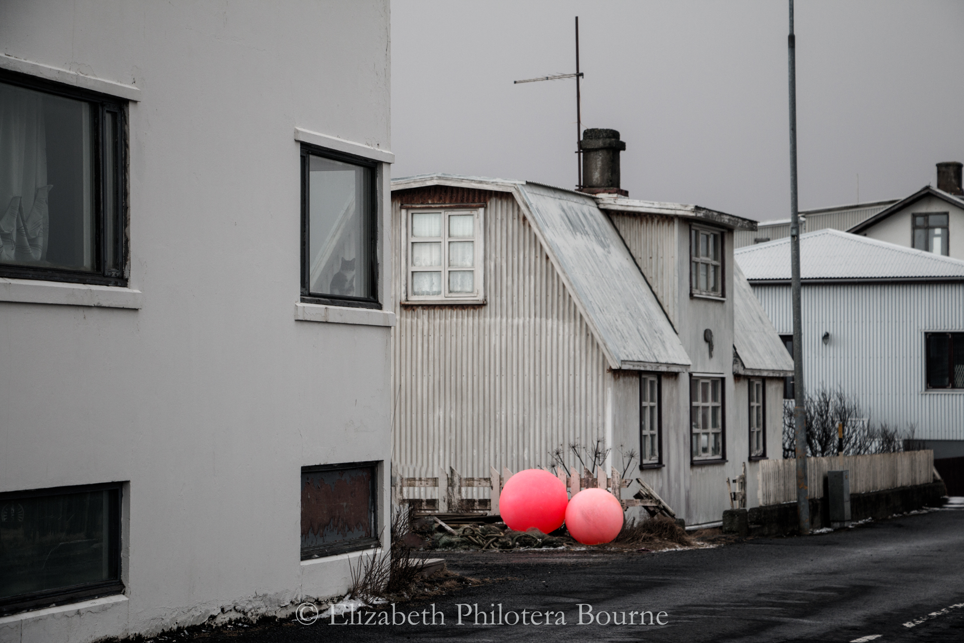 Winter street in Eyrarbakki with gray houses, gray sky, and pink fishing buoys