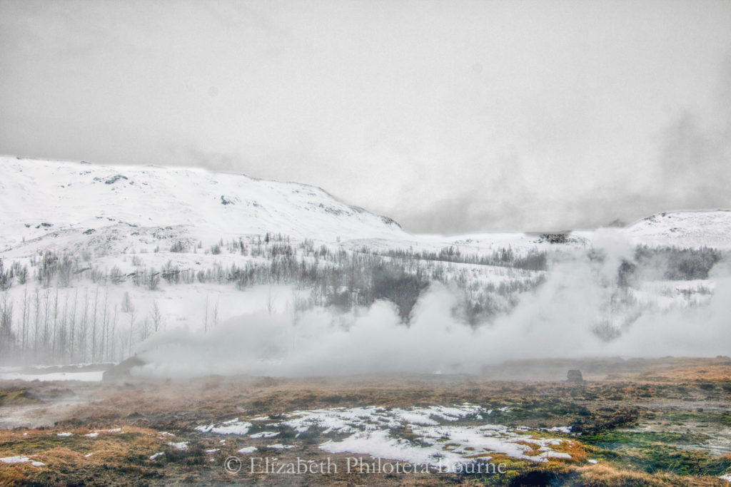 Steam from geysirs rising against snow covered mountains in winter in Iceland