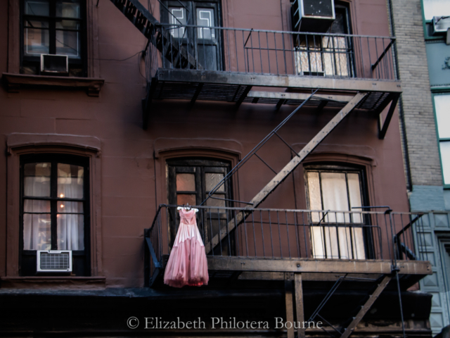 pink formal dress hanging from firescape of brick townhouse in New York
