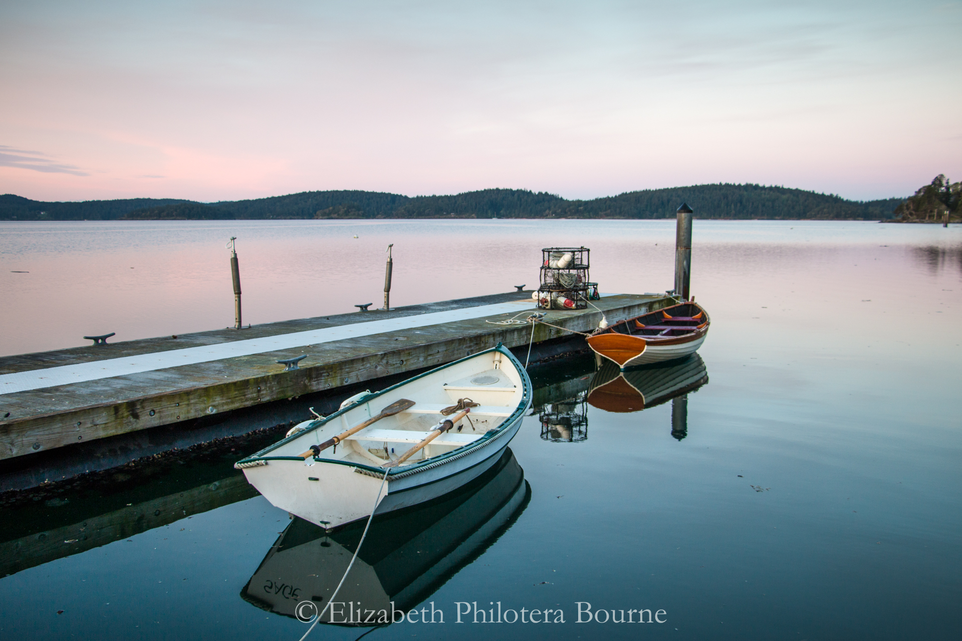 two row boats tied up with water reflections and sunrise