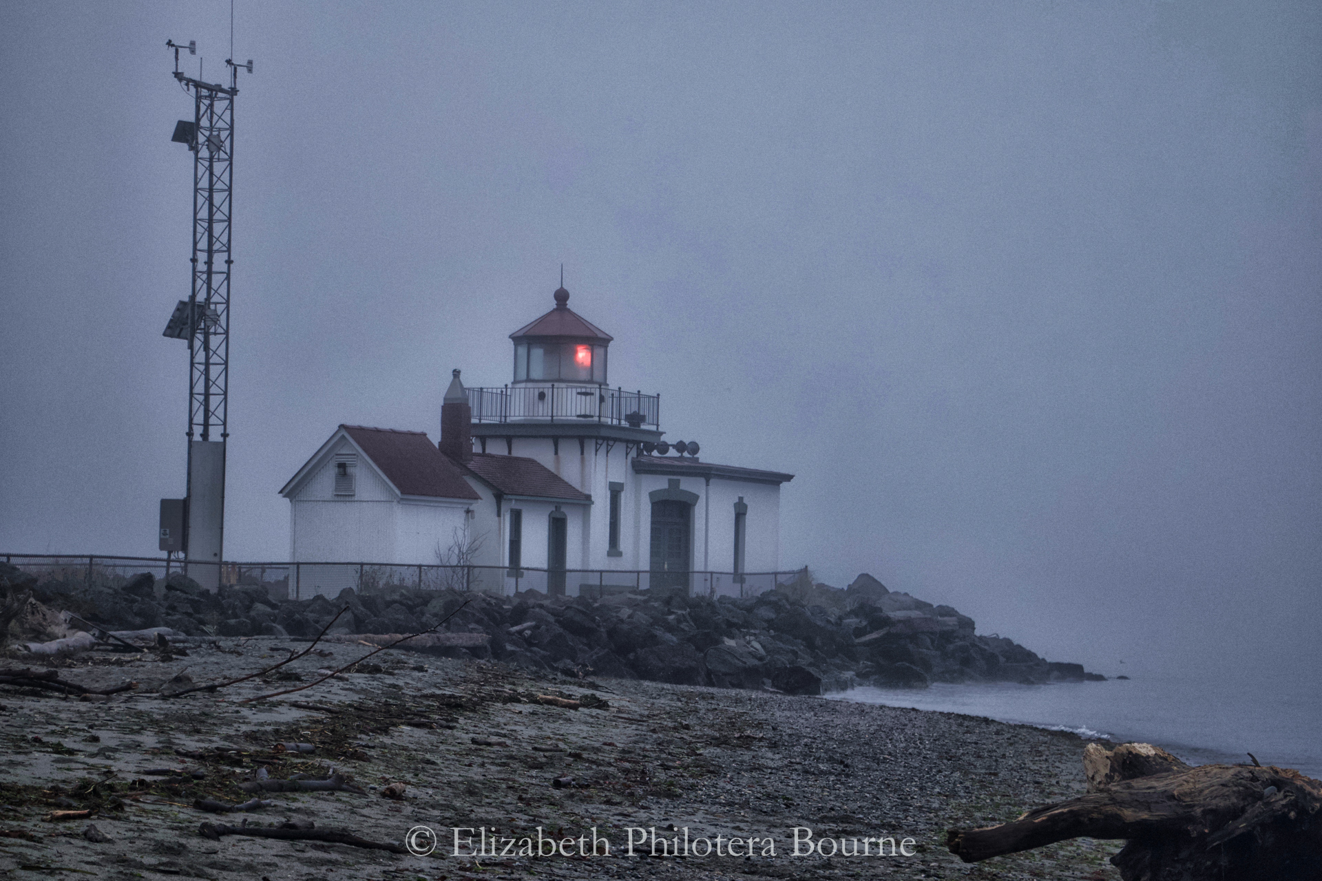 Light house in early morning fog with red light