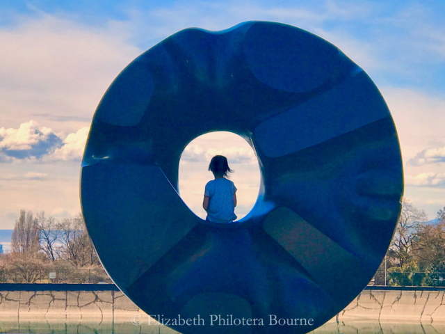 little girl sitting in middle of scuplture looking into distance