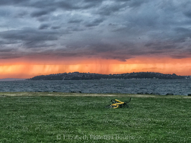 storm at sunset with rain and yellow bike in foreground