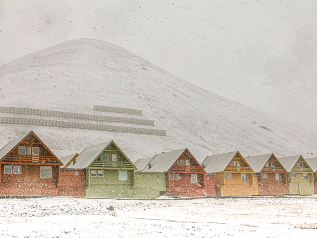 seven colorful painted houses in Longyearbyen Svalbard in front of Sukkerrtoppen in a snowstorm