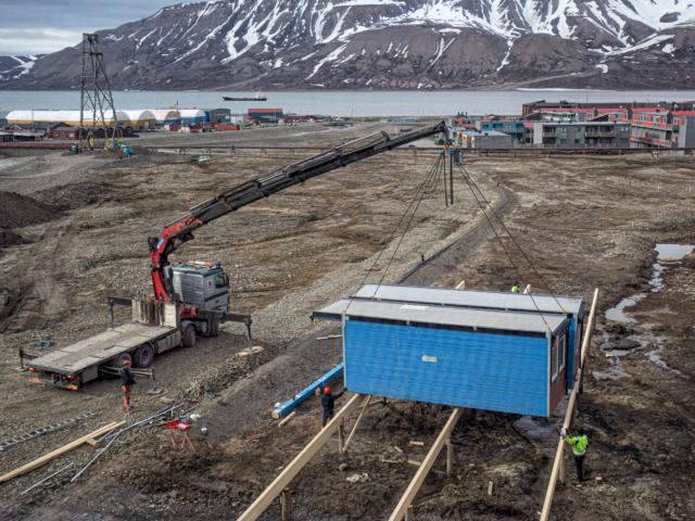 Crane sets blue container housing down for workers' barracks in Longyearbyen Svalbard