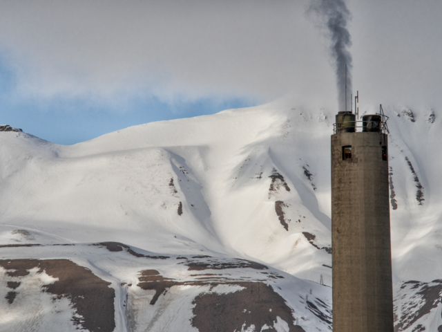 The smoke stack of Norway's last coal burning plant in Longyearbyen Svalbard against the snow covered arctic mountains