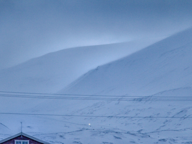 Snowmobile coming home through blue mountains during early spring in Longyearbyen