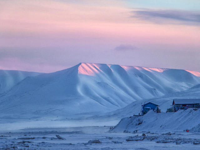 Pastel pink sky and pale blue mountains announce the return of the sun to the high arctic town of Longyearbyen