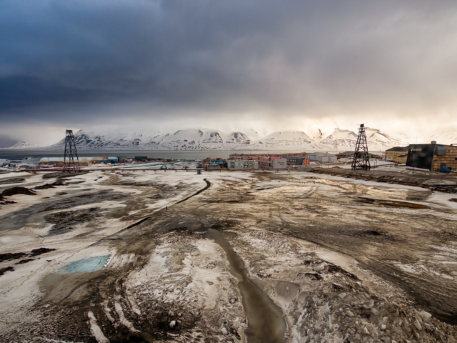 Ice melts in spring revealing the muddy flood plain of the Longyear River in Svalbard
