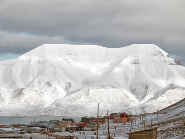 Snow covered mountain in a cloudy sky forms the background for the small arctic town of Longyearbyen