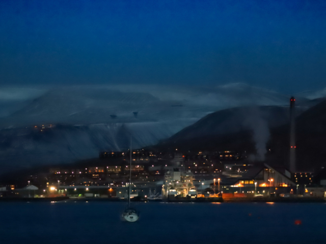 Longyearbyen's night lights glow in orange and yellow against an indigo landscape.