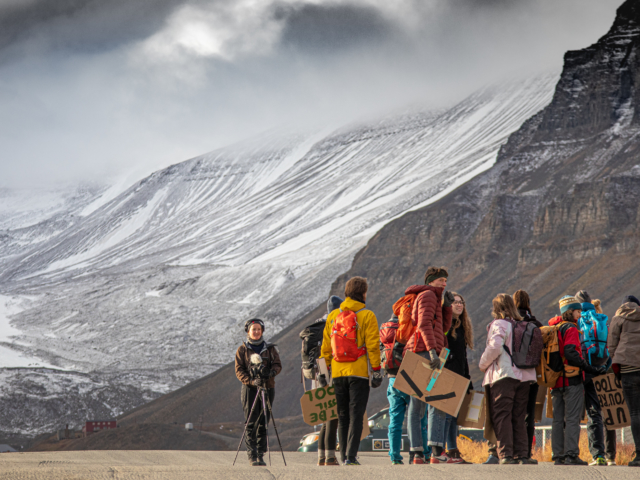 Students in colorful jackets with protest signs being recorded in front of snow covered mountains