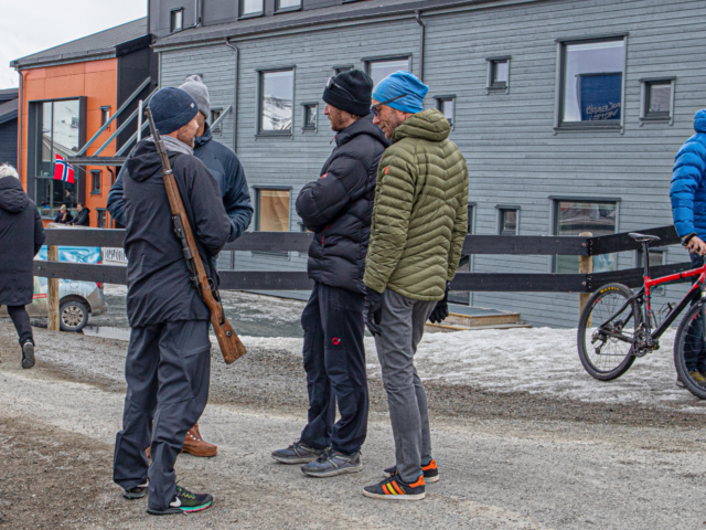 Four men, one with a rifle, standing and talking on a street corner in Longyearbyen