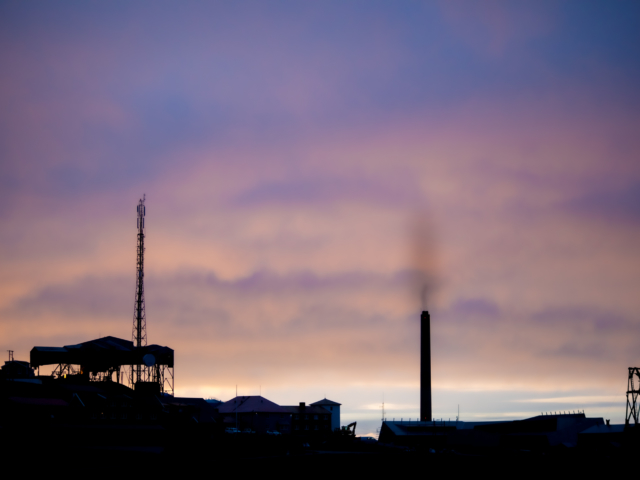Black industrial silhouettes agains one of the last sunset skies.