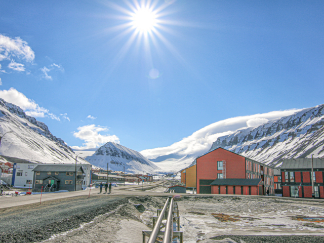 Blue sky and midnight sun shining on the main road in a town in the high arctic