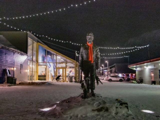 statue of miner on Longyearbyen's main street decorated for Christmas with a red scarf