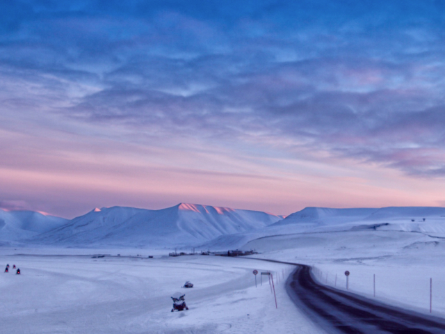 Snowmobiles coming home to Longyearbyen in the magical pastel light of early spring
