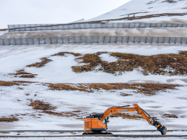 Below the avalanche fence an orange steamshovel works in the area where houses were destroyed by an avalanche in 2015