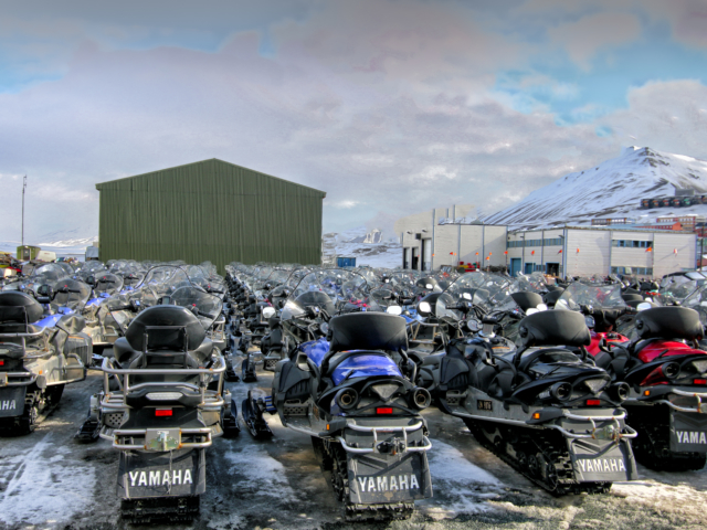 Snowmobiles waiting for tourists behind SSU in Longyearbyen Svalbard