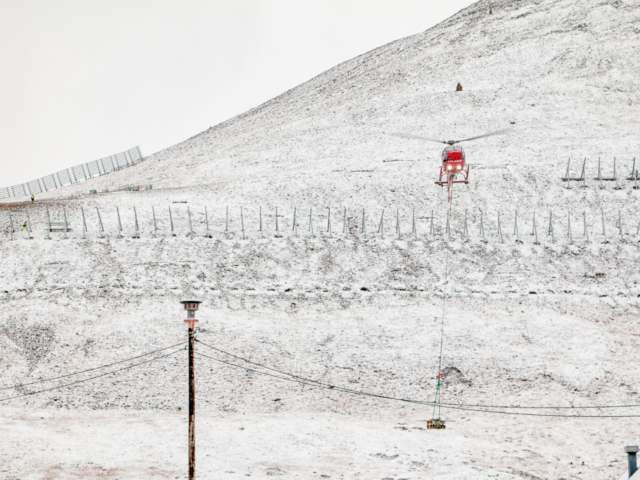 Red helicopter dropping equipment on a snow covered mountain where an avalanche fence is being built